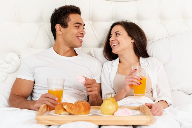 Medium shot couple having breakfast in bed Free Photo