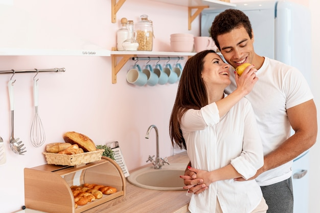 Medium shot couple holding hands in the kitchen Free Photo