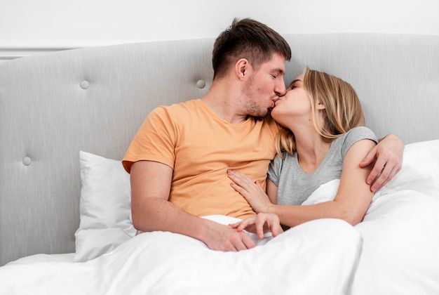 Medium shot couple kissing in the bedroom Free Photo
