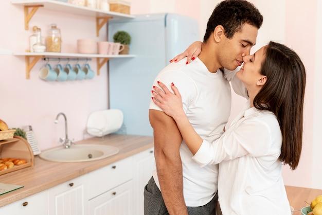 Medium shot couple kissing in the kitchen Free Photo