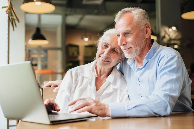 Средний снимок пары смотрит на ноутбук Бесплатные Фотографии
