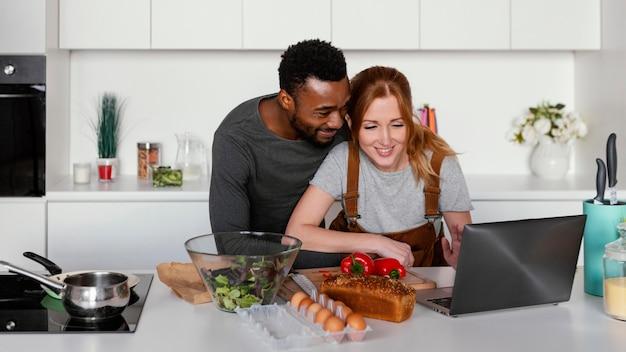 ノートパソコンを見ているミディアムショットのカップル 無料写真