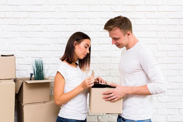 Medium shot couple opening a box Free Photo
