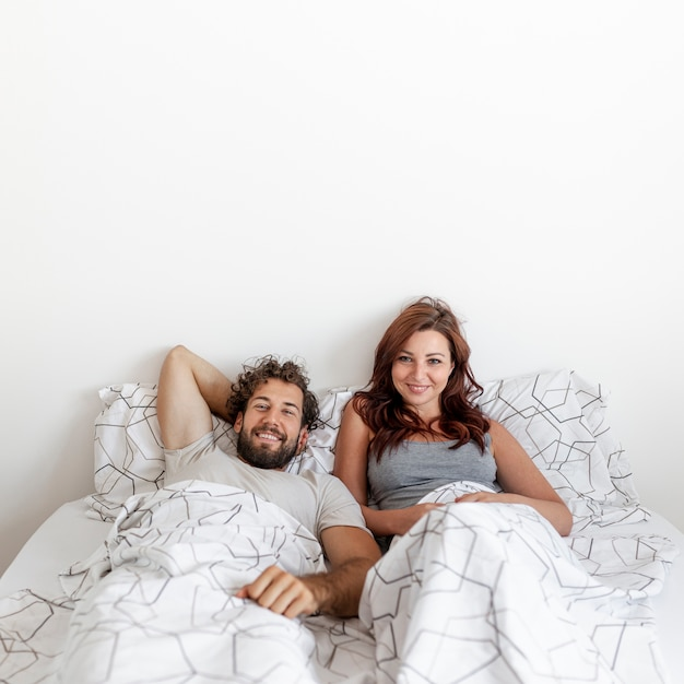 Medium shot of couple relaxing in bed Free Photo
