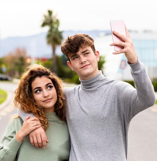 Medium shot couple taking selfie together Premium Photo