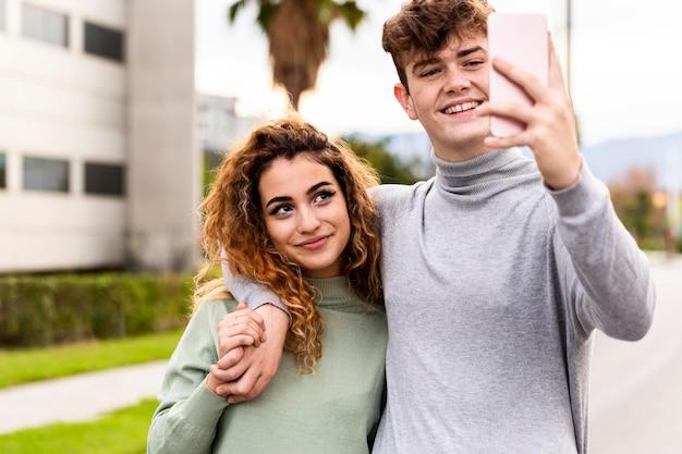 Medium shot couple taking selfie Premium Photo