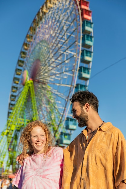 Medium shot couple with carnival wheel Free Photo