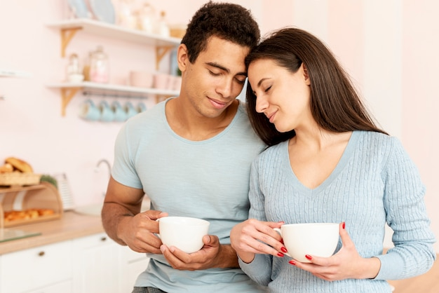 Medium shot couple with mugs in the kitchen Free Photo