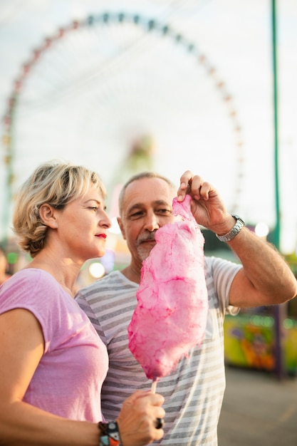 Medium shot couple with pink cotton candy Free Photo