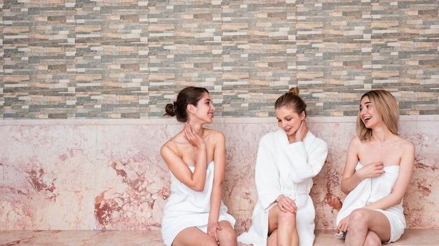 Medium shot cute girls with robes indoors Free Photo