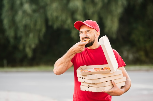 Medium shot delivery guy eating pizza Free Photo