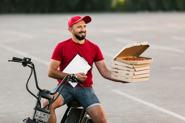 Medium shot delivery guy holding up boxes with pizza Free Photo