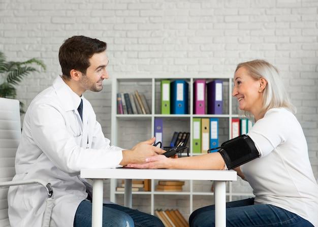 Medico del colpo medio che prende la pressione sanguigna del paziente Foto Gratuite