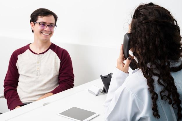 Medico del colpo medio che parla sul telefono Foto Gratuite