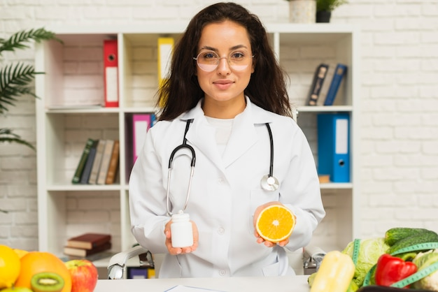 Medium shot doctor with stethoscope and orange Free Photo