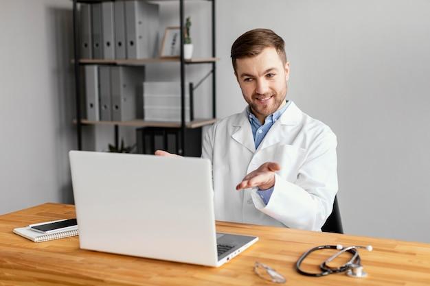 Medico del colpo medio che lavora alla scrivania Foto Gratuite
