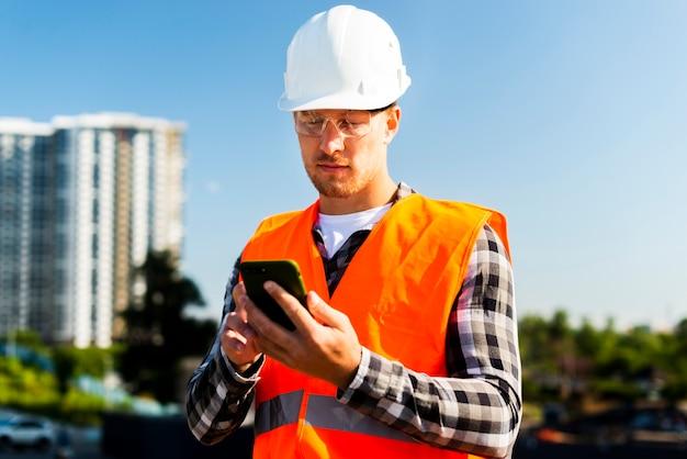 Medium shot of engineer looking at phone Free Photo