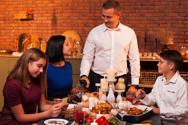 感謝祭のテーブルでミディアムショットの家族 Premium写真