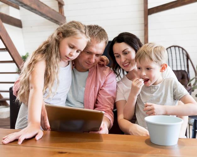 タブレットを見てミディアムショットの家族 無料写真