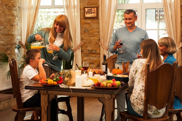 Семья среднего кадра сидит за столом Бесплатные Фотографии