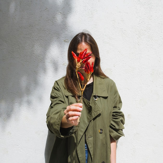 Medium shot fashion woman covering her face with bunch of peppers Free Photo