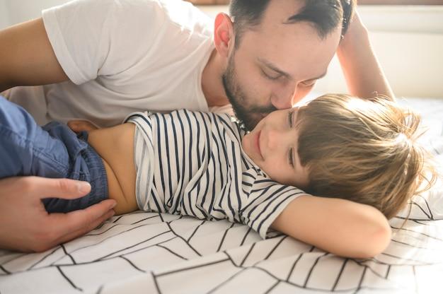 Средний выстрел отец целует сына Бесплатные Фотографии