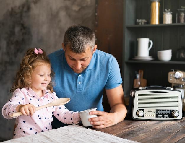 ミディアムショットの父が台所で娘と一緒に座っています。 無料写真