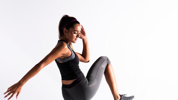 Medium shot fit girl in gym suit exercising indoors Free Photo