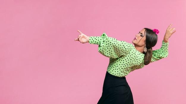 Medium shot flamenca performing floreo on pink background Free Photo