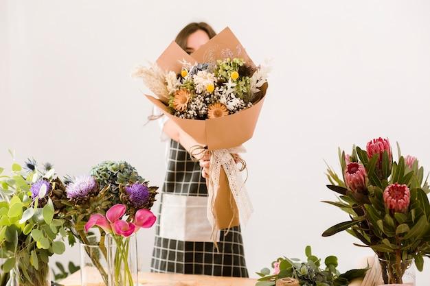 Medium shot florist holding up a beautiful bouquet Free Photo