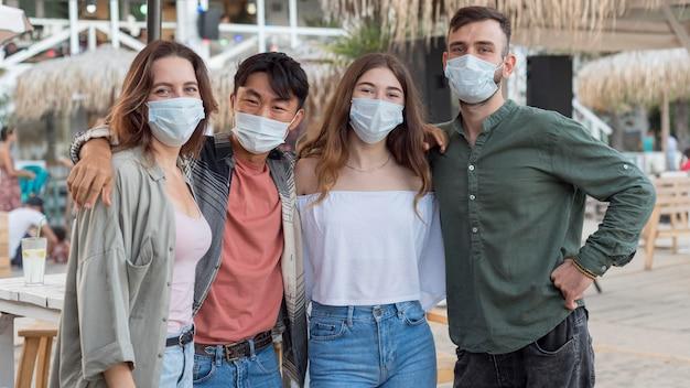 Друзья среднего кадра позируют в масках Бесплатные Фотографии