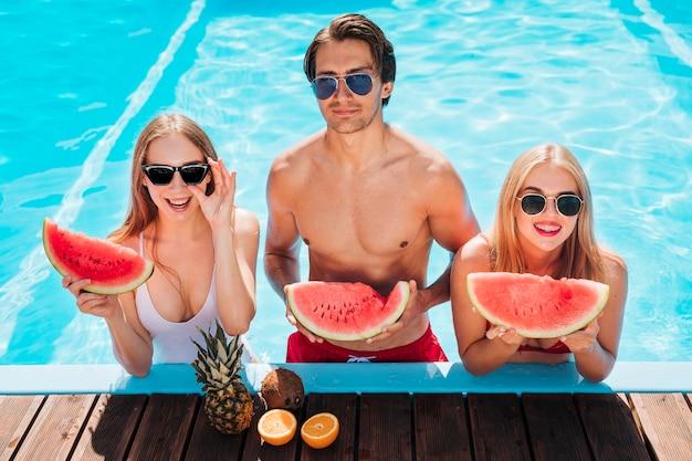Medium shot friends posing with watermelon Free Photo