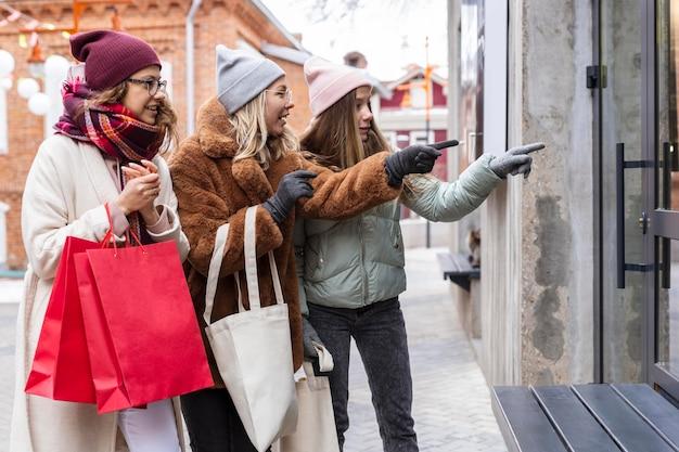중간 샷 친구와 쇼핑백 무료 사진