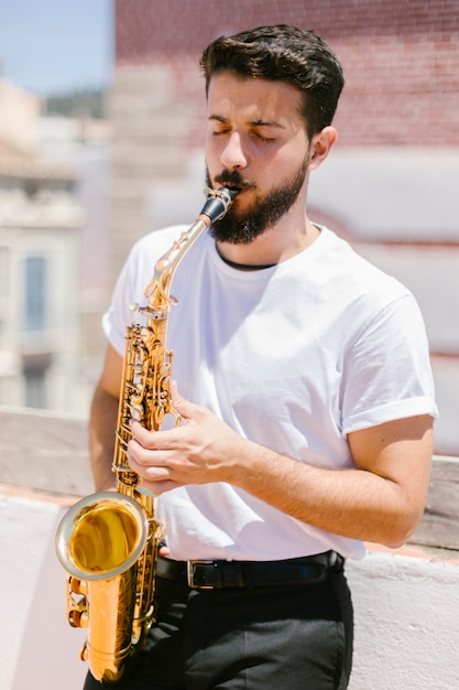 Medium shot front view musician playing the saxophone Free Photo