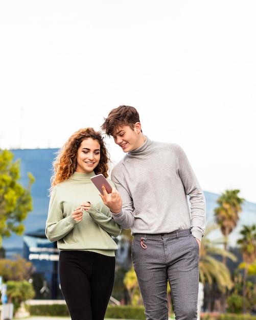 Medium shot girl and boy with smartphone Premium Photo