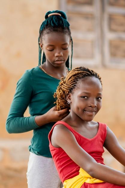 중간 샷 여자 아이 꼬기 친구의 머리 무료 사진
