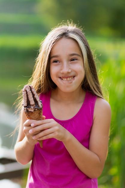 Colpo medio della ragazza che mangia il gelato Foto Gratuite