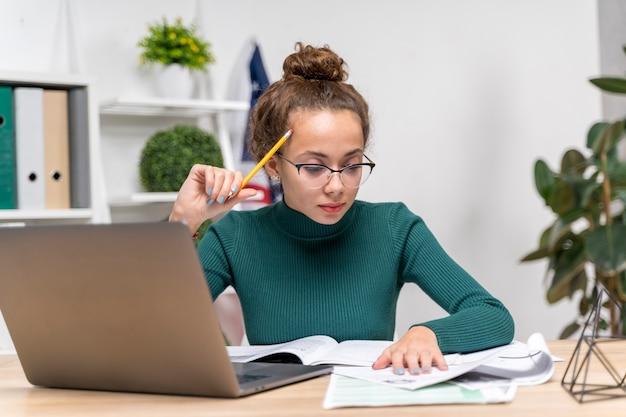 Medium shot girl focusing at studying Free Photo