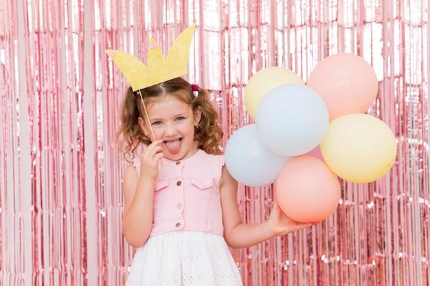 Medium shot girl holding colorful balloons Free Photo