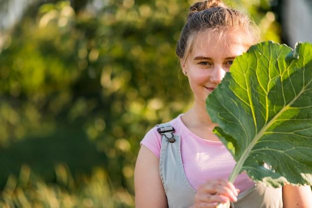 Средний снимок девушка держит лист салата Бесплатные Фотографии