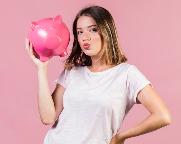 Medium shot girl holding a piggy bank Free Photo