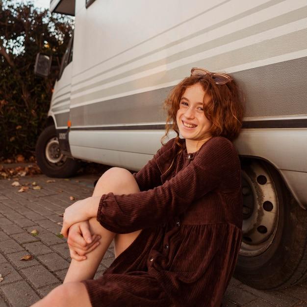 バンの近くでポーズをとるミディアムショットの女の子 無料写真