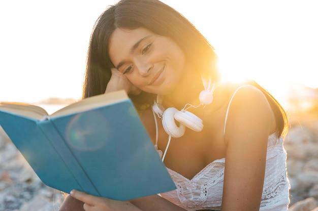 Medium shot girl reading book Free Photo