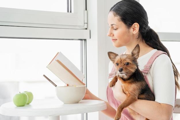 Ragazza del colpo medio che legge con il cane Foto Gratuite