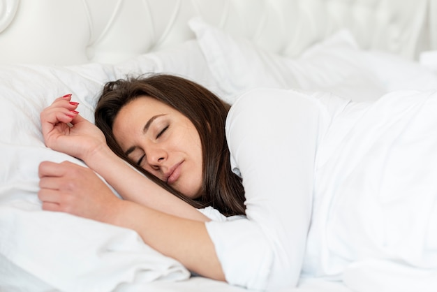 Medium shot girl sleeping in comfortable bed Free Photo