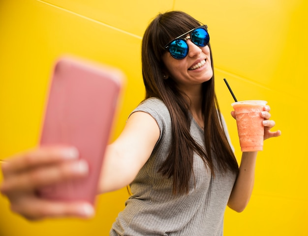 Medium shot girl with drink taking a selfie Free Photo