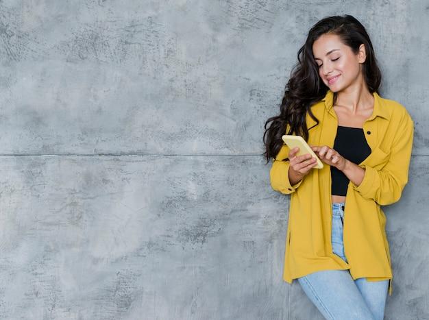 携帯電話とセメントの背景を持つミディアムショット少女 無料写真