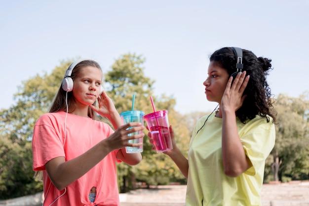 Ragazze di tiro medio che ascoltano musica Foto Gratuite