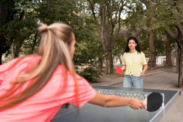 Девушки среднего роста играют в настольный теннис Бесплатные Фотографии