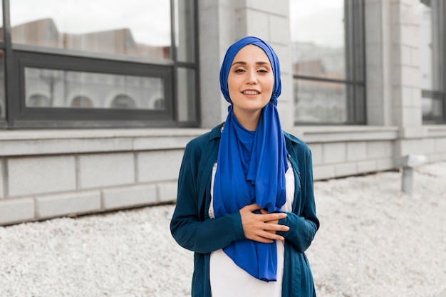Medium shot gorgeous girl with hijab smiling outside Free Photo